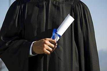 Male graduate holding diploma