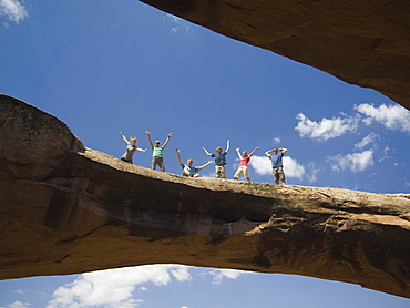 People cheering on rock formation