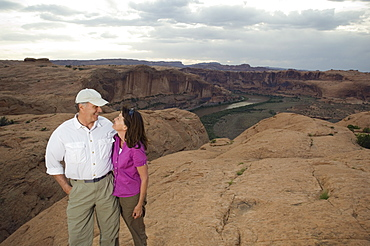 Couple smiling at each other on rock formation