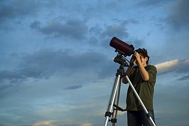 Man using telescope on tripod
