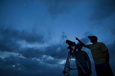 Couple using telescope on tripod