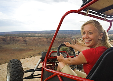 Woman in off-road vehicle at edge of cliff