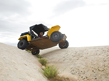 People in off-road vehicle on rock formation
