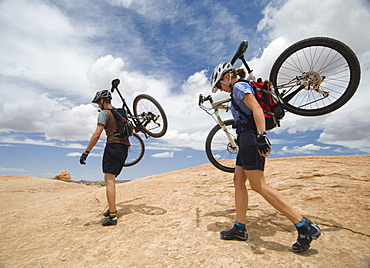 Couple carrying mountains bikes in desert
