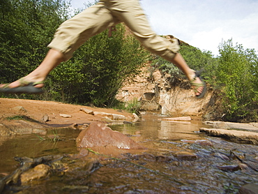 Woman jumping over stream