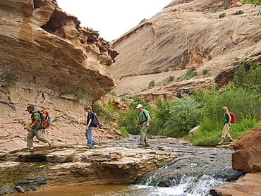 People hiking over stream