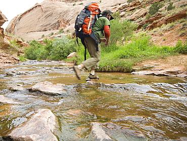 Man hiking through stream