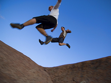 Men jumping over rock formations