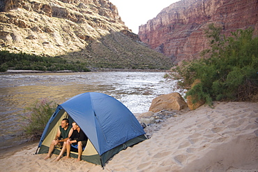 Couple in tent next to river, Colorado River, Moab, Utah, United States