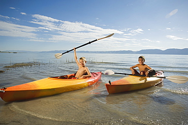 Brothers paddling in canoes on lake, Utah, United States