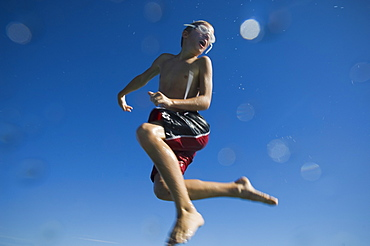 Boy in bathing suit jumping in air, Utah, United States