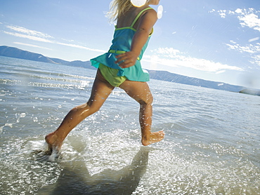 Girl running in water, Utah, United States