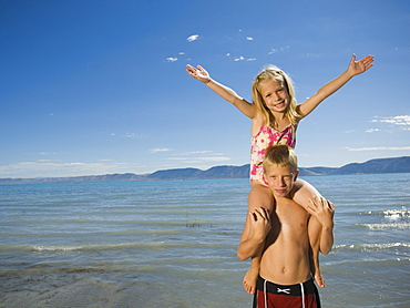 Girl sitting on brother's shoulders, Utah, United States