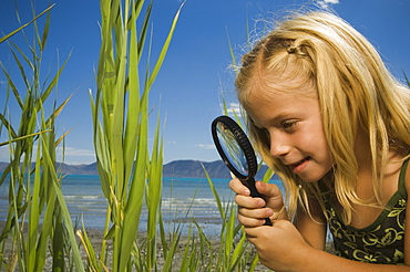 Girl looking through magnifying glass, Utah, United States