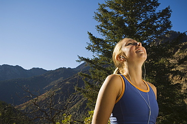 Woman listening to mp3 player, Utah, United States