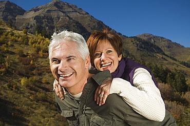 Senior man giving wife piggy back ride, Utah, United States