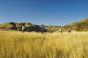 Group of people running in field, Utah, United States
