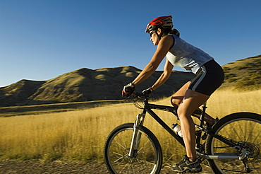 Woman riding mountain bike, Salt Flats, Utah, United States