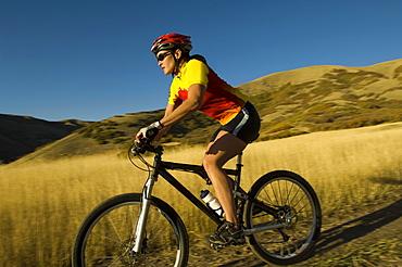 Woman riding mountain bike, Salt Flats, Utah, United States