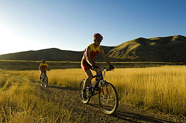 Couple riding mountain bikes, Salt Flats, Utah, United States