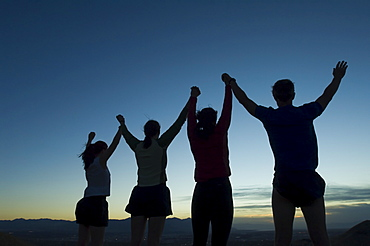 Silhouette of people with arms raised, Salt Flats, Utah, United States