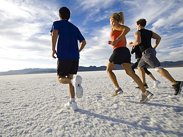 Group of people running on salt flats, Utah, United States
