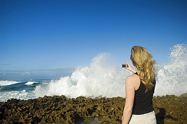 Woman taking photograph of ocean, Oahu, Hawaii, United States
