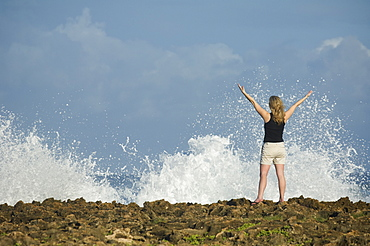 Woman with arms raised in front of ocean, Oahu, Hawaii, United States