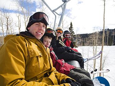 Family sitting on ski lift chair