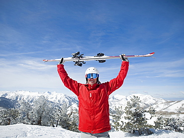Man holding skis over head