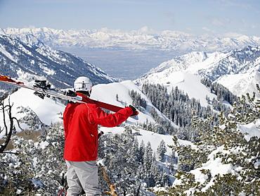 Man holding skis on shoulder