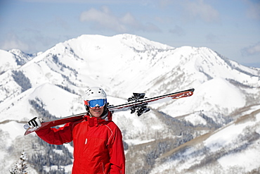 Man holding skis on shoulder