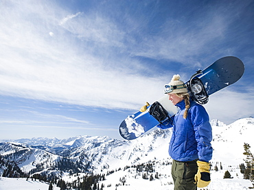 Woman holding snowboard, Wasatch Mountains, Utah, United States