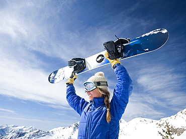 Woman holding snowboard over head