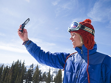 Woman in ski gear taking photograph