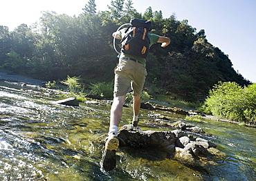 Man jumping across river on rocks