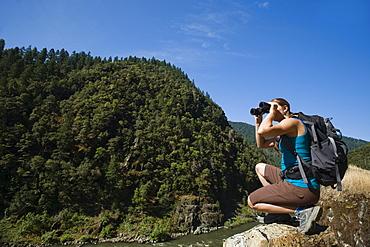 Hiker looking through binoculars on river overlook