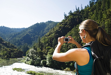 Hiker photographing river scene