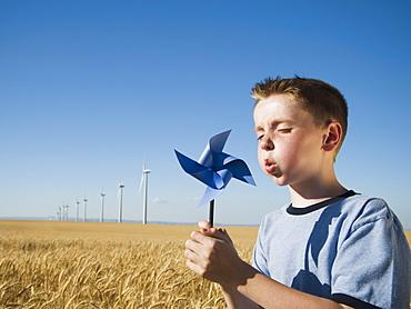 Boy holding pinwheel on wind farm