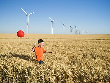Boy running with balloon on wind farm
