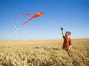Boy running with kite on wind farm