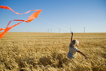 Girl running with kite on wind farm