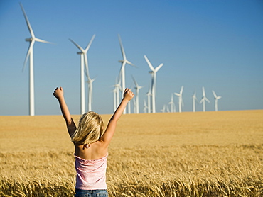 Girl with arms raised on wind farm