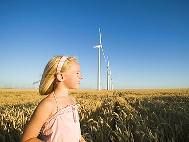 Girl in tall wheat field on wind farm