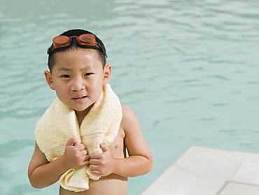 Boy wrapped in towel posing in front of swimming pool