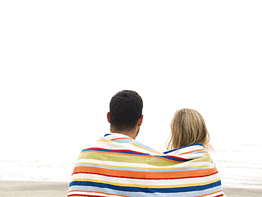 Couple wrapped in towel on beach