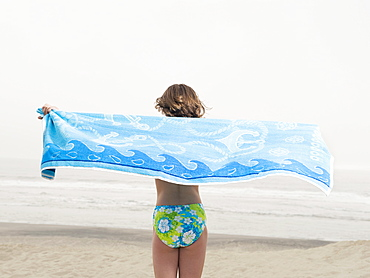 Girl holding towel on beach
