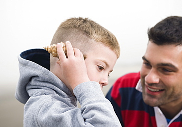 Father watching son hold seashell up to ear