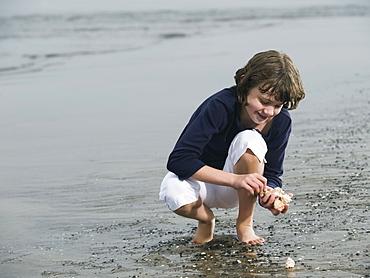Girl finding seashells on beach