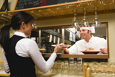 Chef giving waitress plates of food